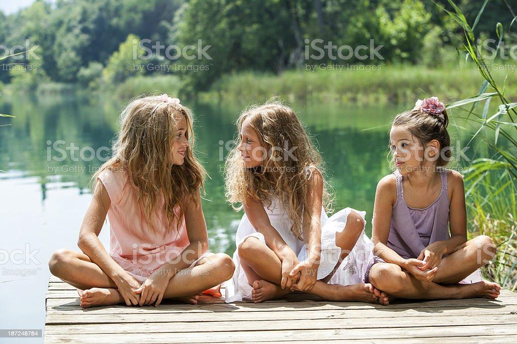 Trois fille amis assis sur la jetée du lac. photo libre de droits