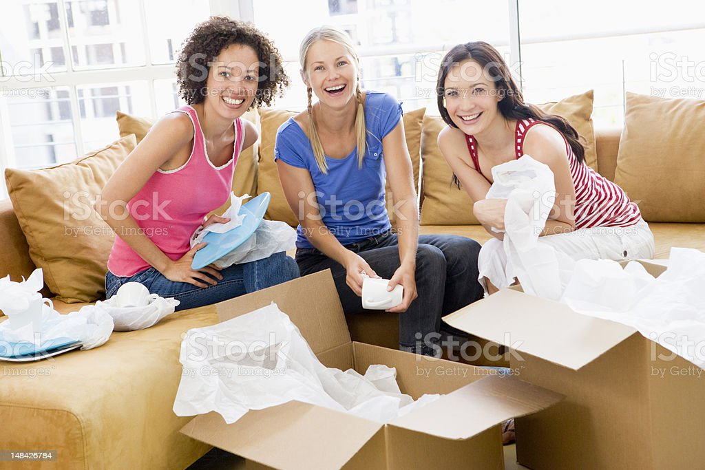 Three girl friends unpacking boxes in new home smiling stock photo
