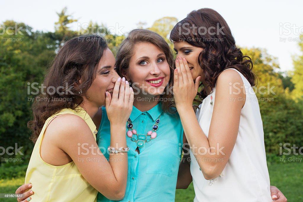 three girlfriends gossip and surprised stock photo