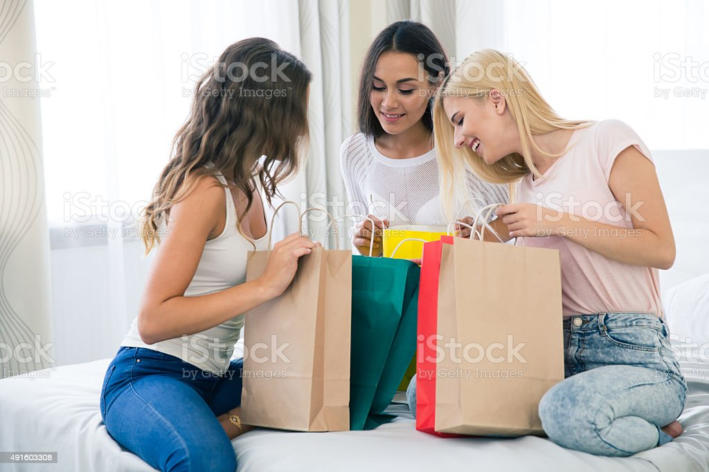 Three girlfriends with many shopping bag stock photo
