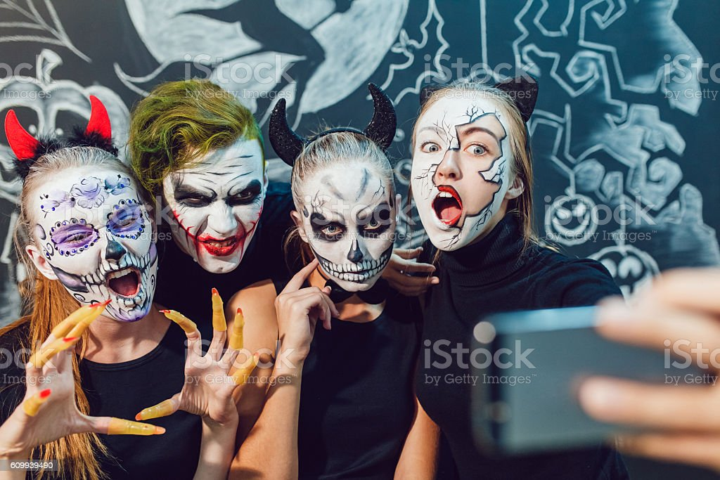 Three girls and a guy going on Halloween, grimace  make stock photo