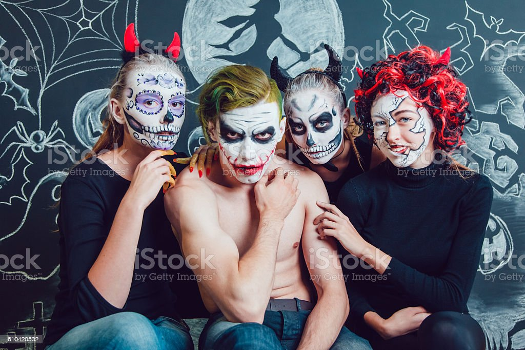 Three girls and a guy with Halloween face art on stock photo