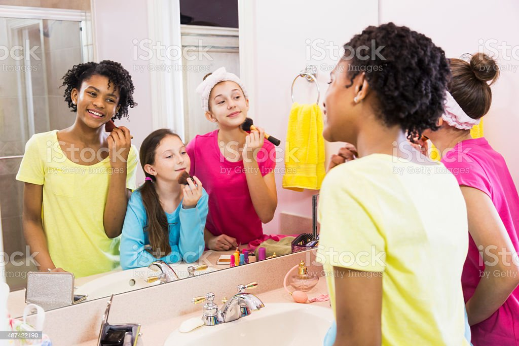 Three girls at sleepover putting on makeup in bathroom stock photo