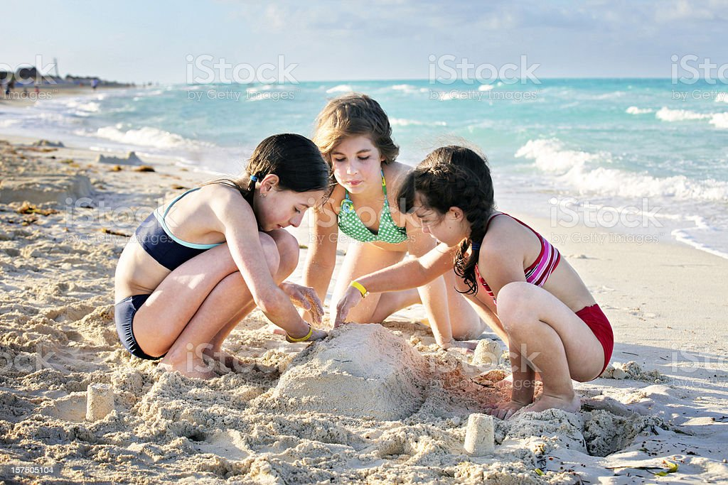 Three girls building a sand castle horizontal royalty-free stock photo