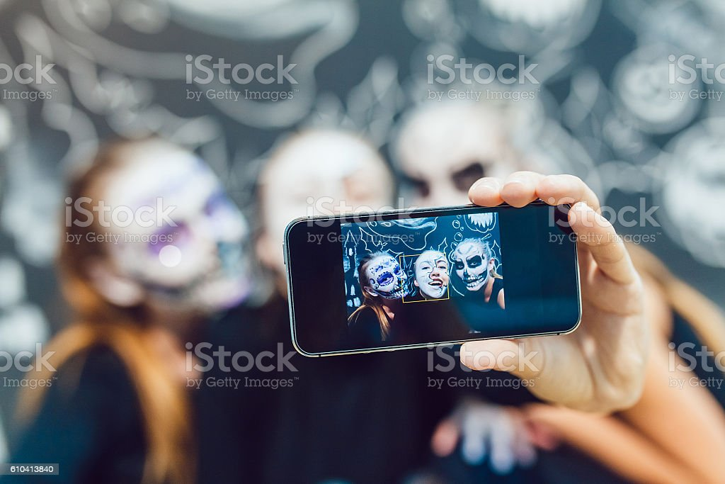 Three girls going on Halloween, grimace make selfie  a dark stock photo