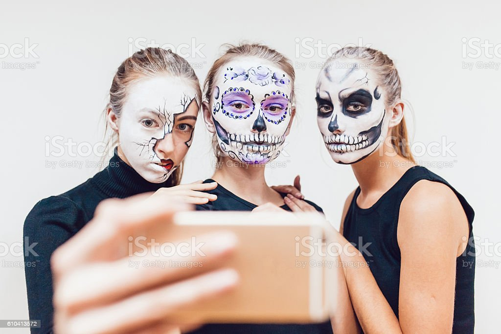 Three girls going on Halloween, grimace make selfie  white background stock photo