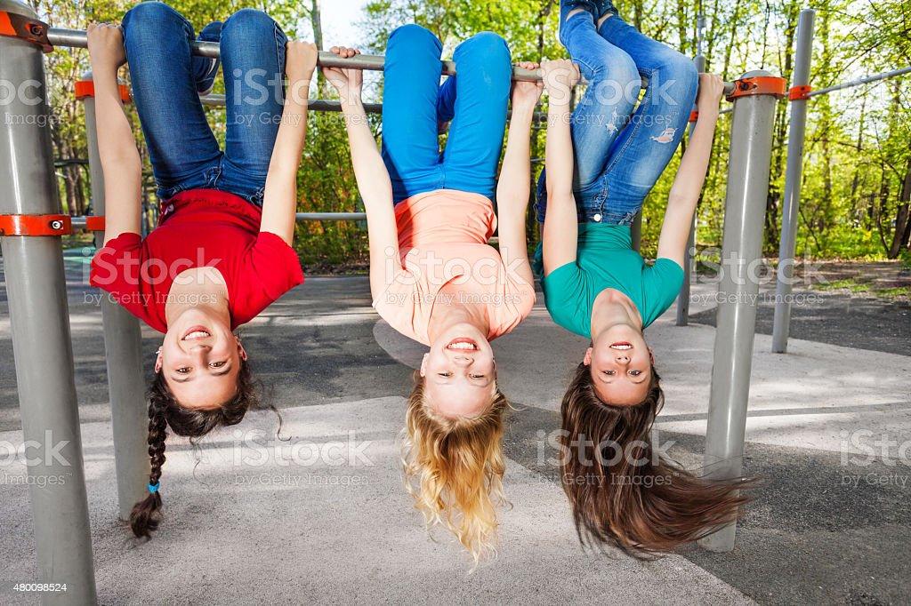 Three girls hanging upside-down on brachiating bar stock photo