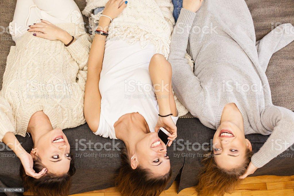 Three girls having fun, lying on bed stock photo