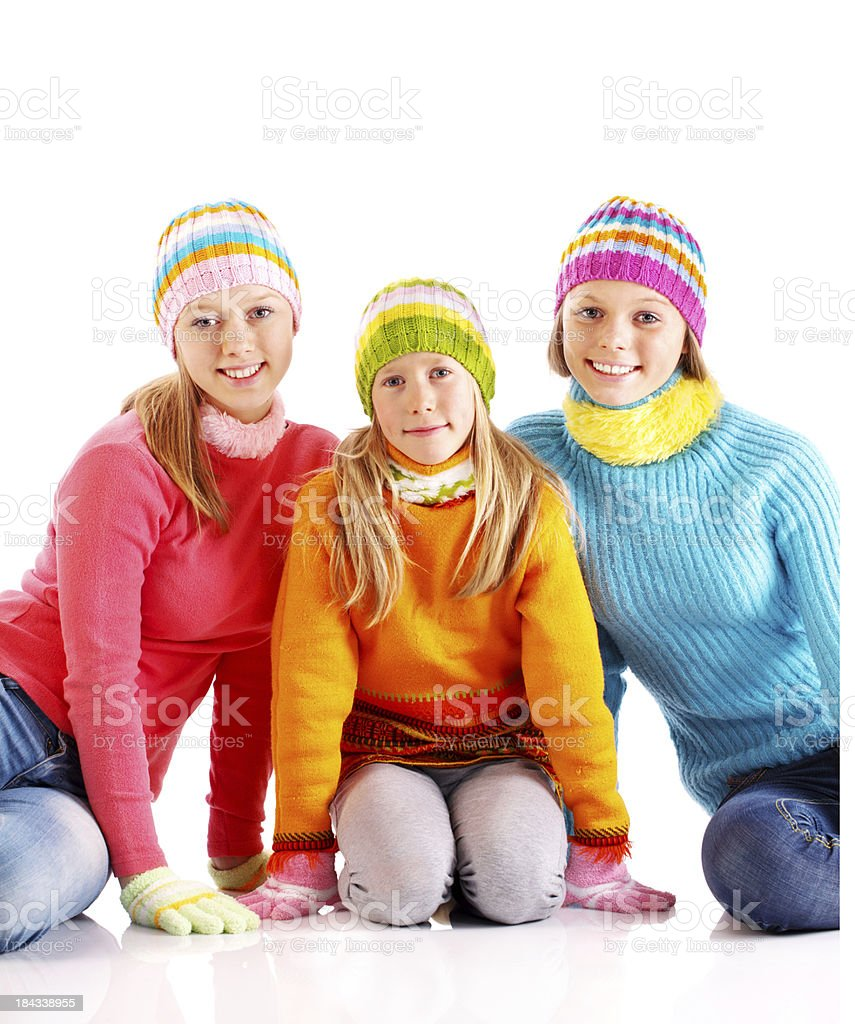 Three girls in colorful cardigans looking at the camera. royalty-free stock photo