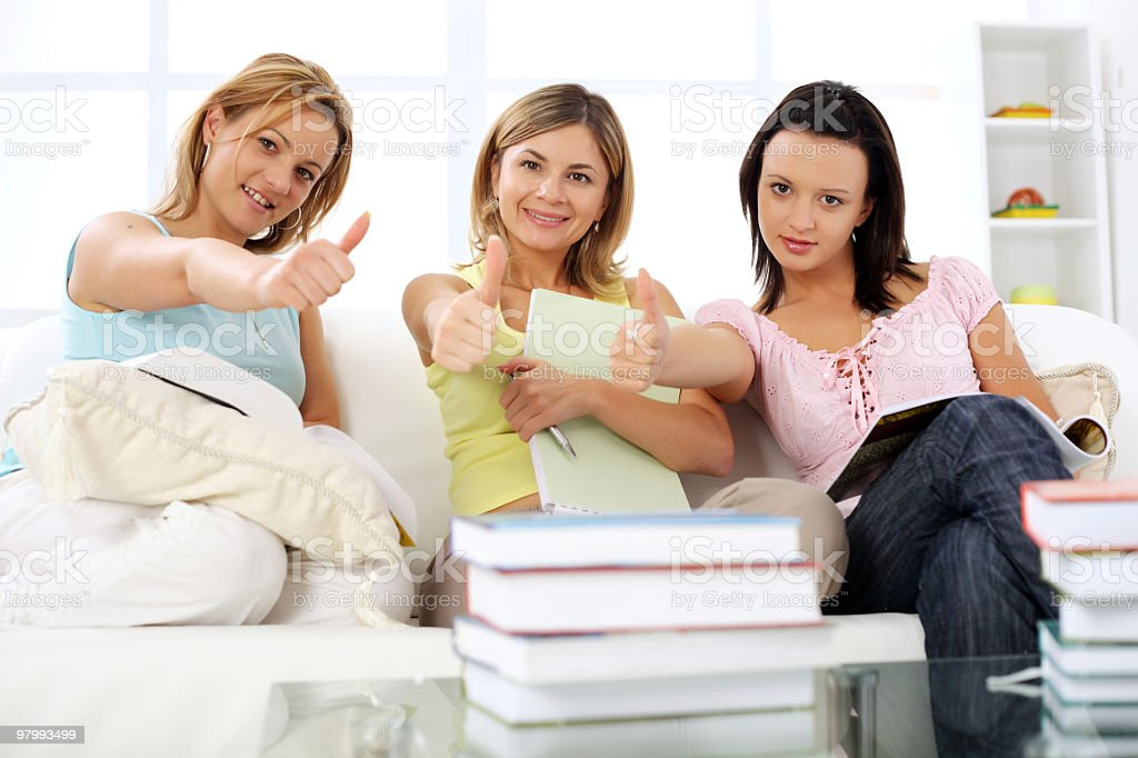 Three girls in living room with many books. royalty-free stock photo