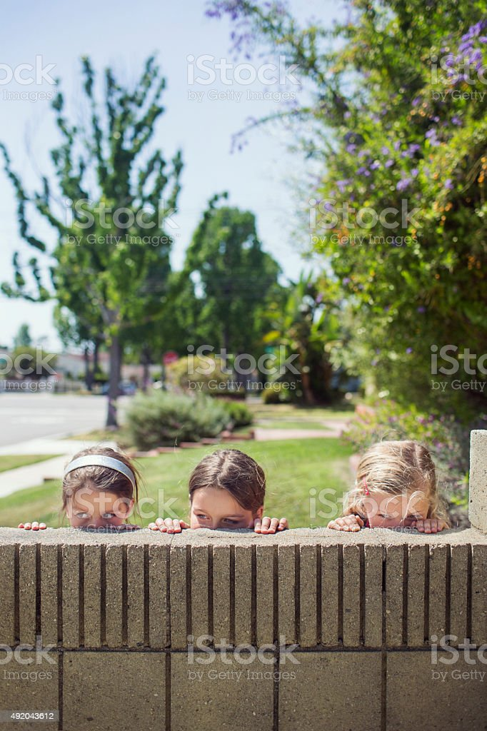 Three girls peeping over a wall stock photo