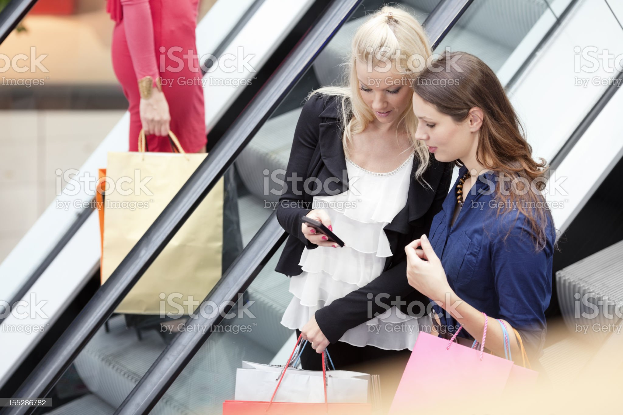 three girls  standing on escalator, carrying shopping bags royalty-free stock photo