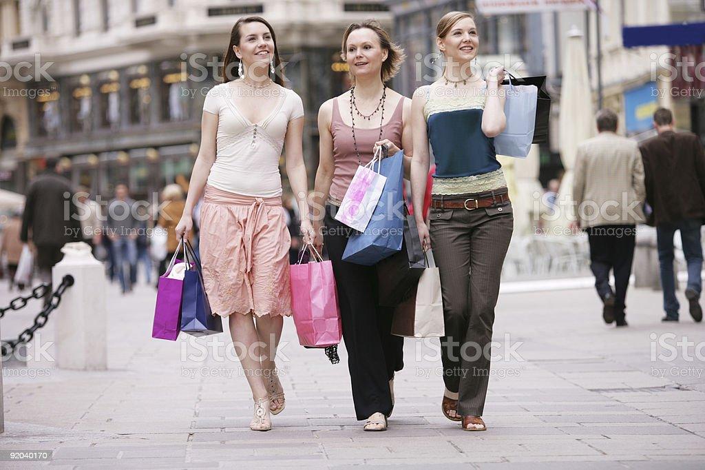 Three girls walking a street holding clothing shopping bags stock photo