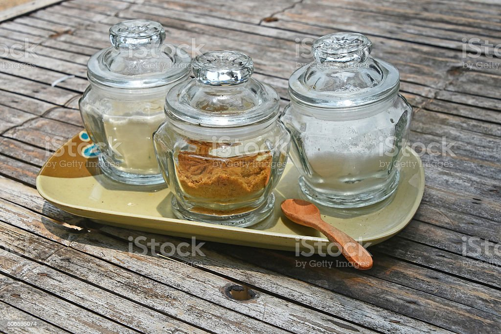 Three glass jars of sugar on bamboo table royalty-free stock photo