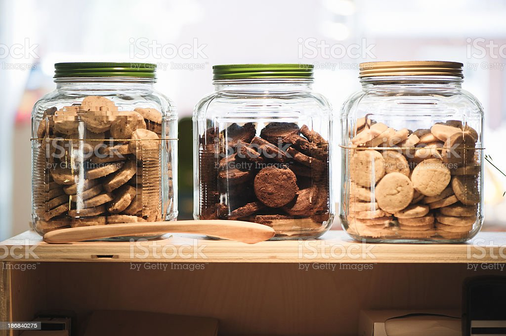Three glass transparent cookie jars on wooden shelf. royalty-free stock photo