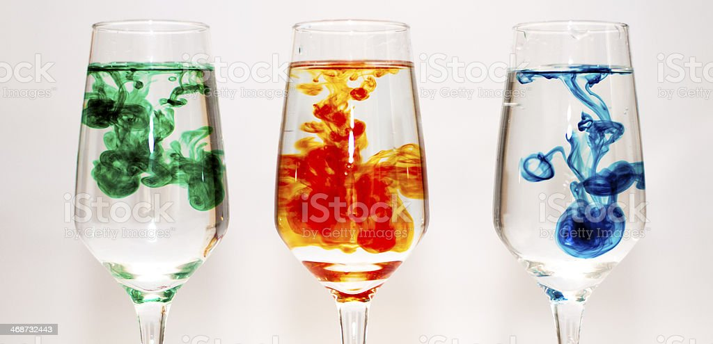 Three glasses filled with water and food colourings stock photo