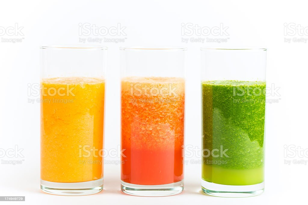 Three glasses holding yellow, red and green smoothies royalty-free stock photo