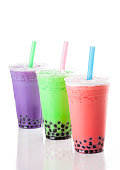 Three glasses of colourful bubble tea, with straws.