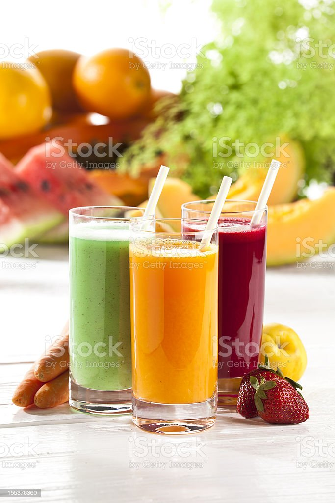 Three glasses of fruit juice with fruits in the background stock photo
