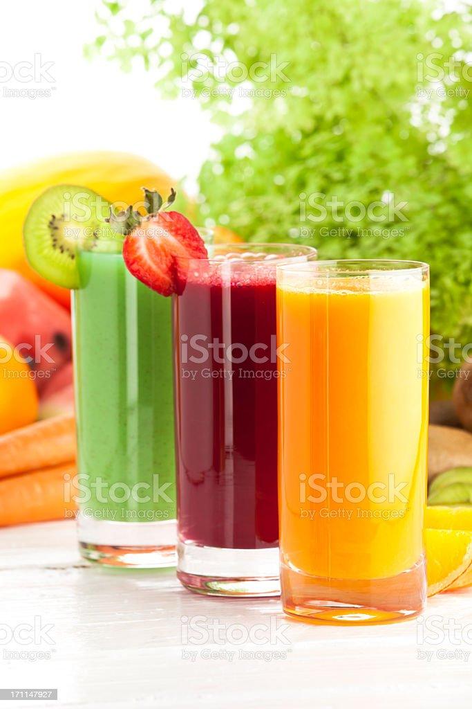 Three glasses of fruit juices on white garden table stock photo