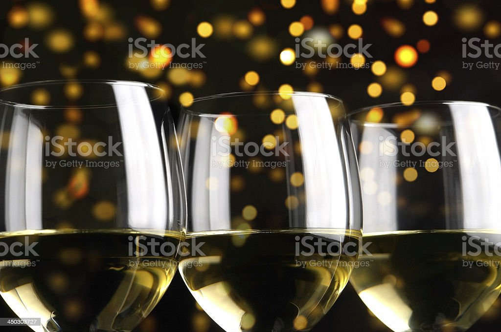 Three Glasses of White Wine against sparkling yellow lights stock photo