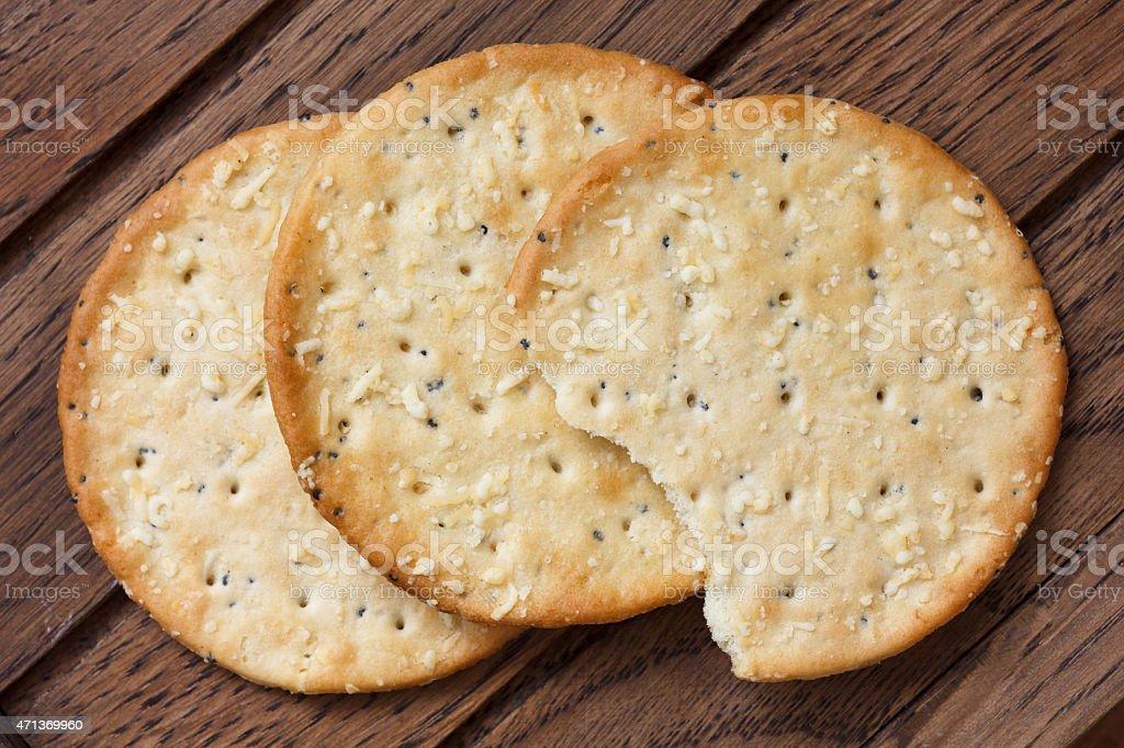 Three golden cheese crackers on dark wood. stock photo