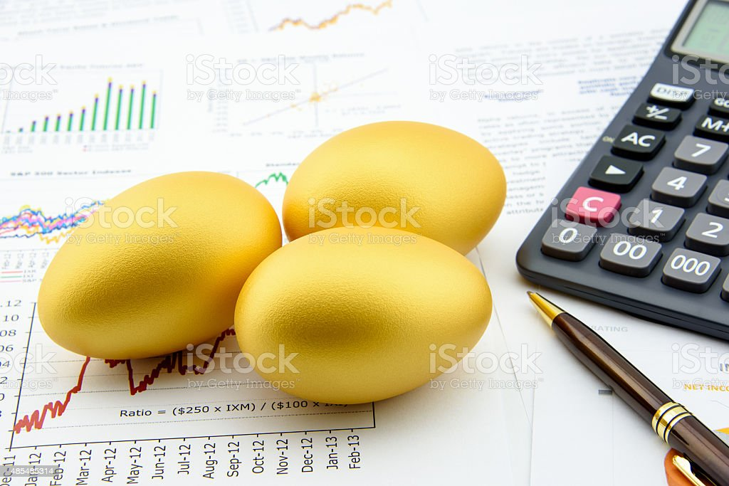Three golden eggs with a calculator on financial reports. stock photo