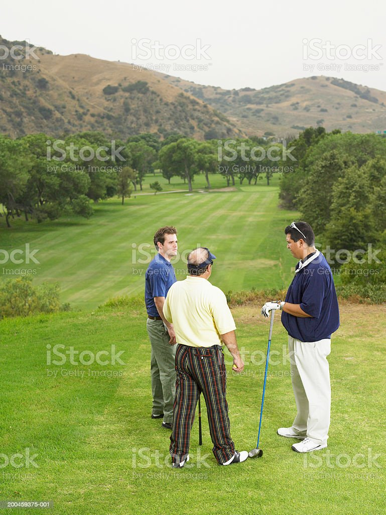 Three golfers talking on green royalty-free stock photo
