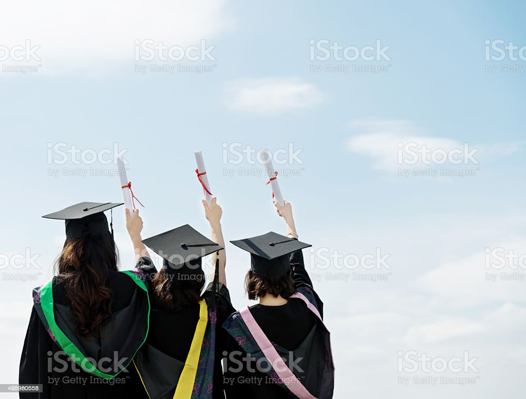 Three graduate students holding diplomas stock photo