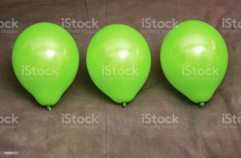Three green balloons against brown wallpaper royalty-free stock photo