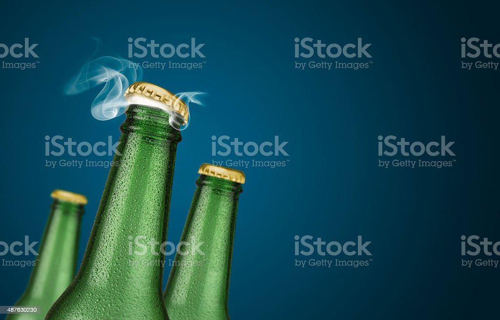 Three green beer bottles on blue background stock photo