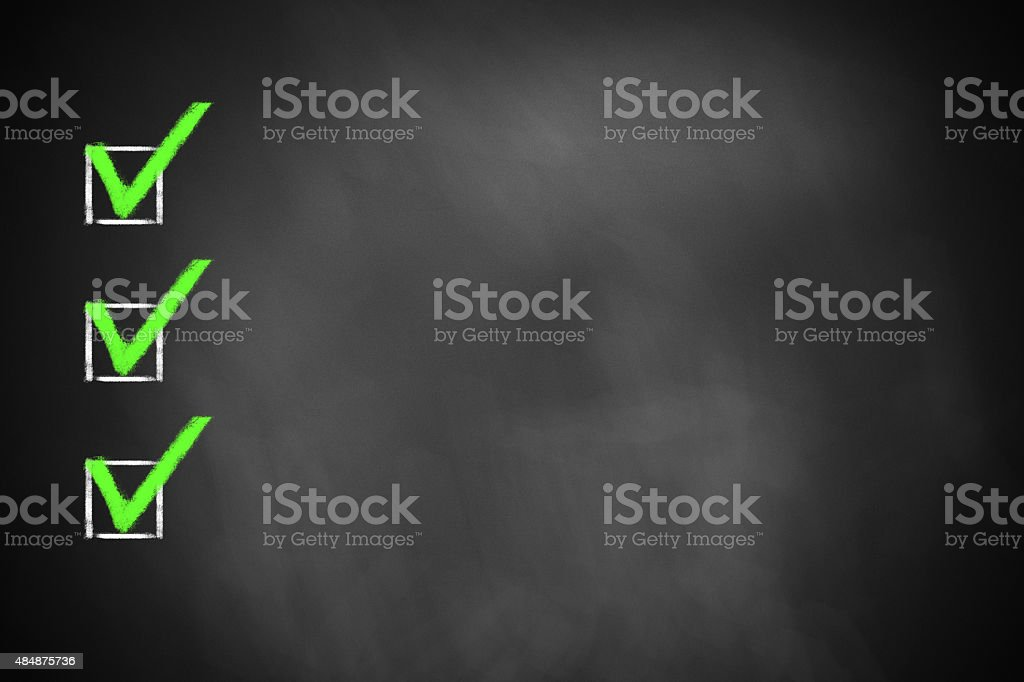 three green marked checkboxes on  chalkboard stock photo