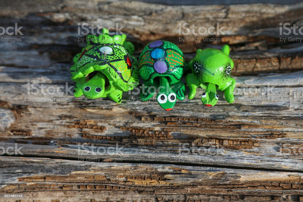 Three green wooden toys on a dead log stock photo