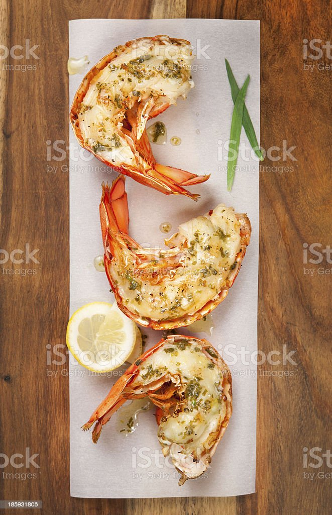 Three grilled lobster tails on a plate stock photo