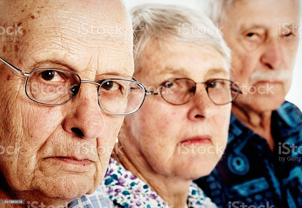 Three grumpy seniors, two men, one woman, frowning, disappointed stock photo