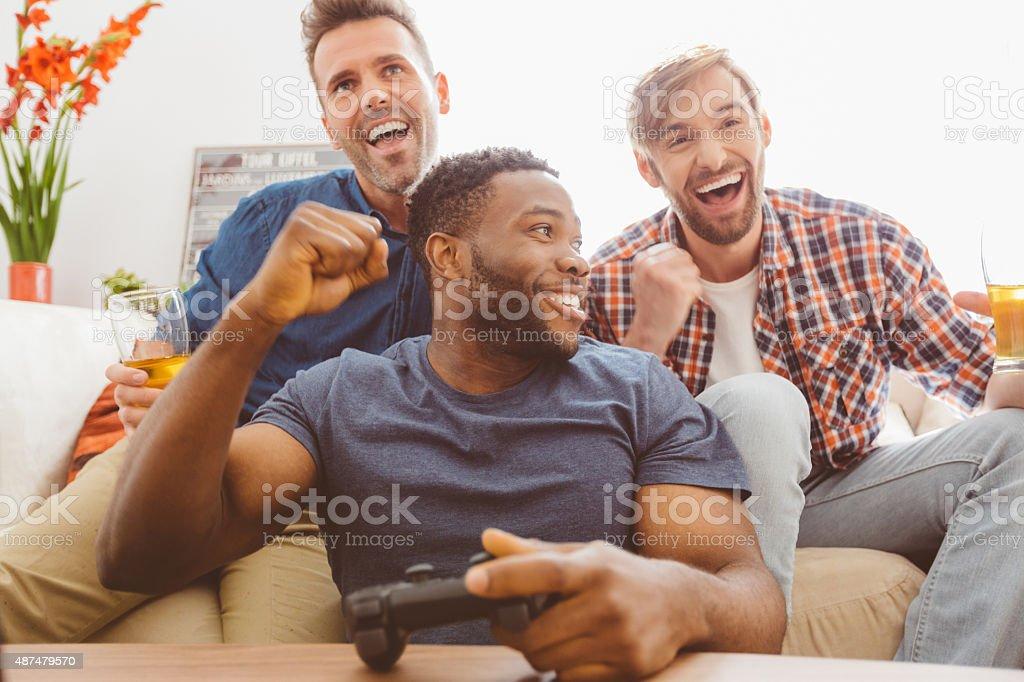 Three guys playing video games stock photo
