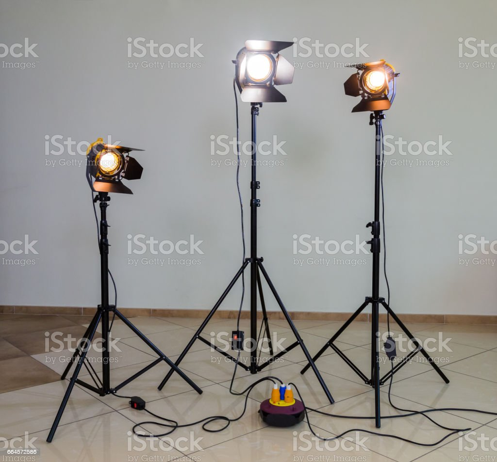 Three halogen spotlights with Fresnel lenses on a grey background. Photographing and filming in the interior. Lighting equipment for movie production stock photo
