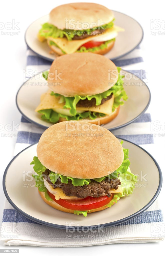 three hamburgers on plates royalty-free stock photo