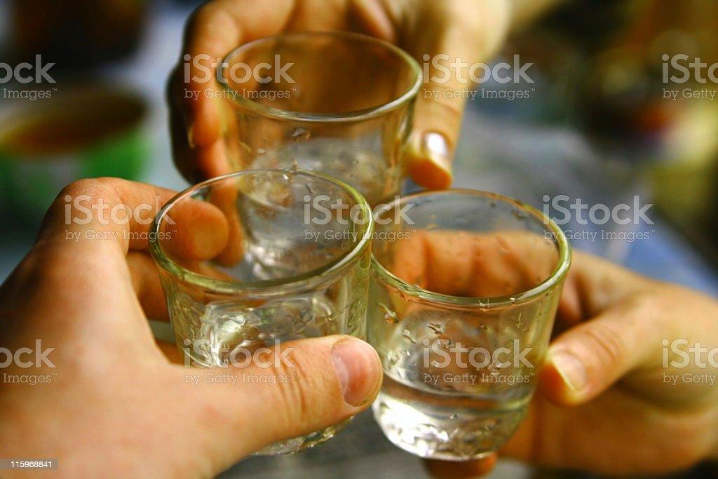 Three hands holding shot glasses of Russian vodka stock photo