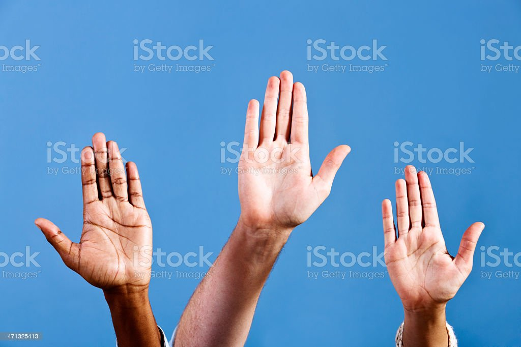 "Three hands make ""Stop"" gesture against blue royalty-free stock photo"