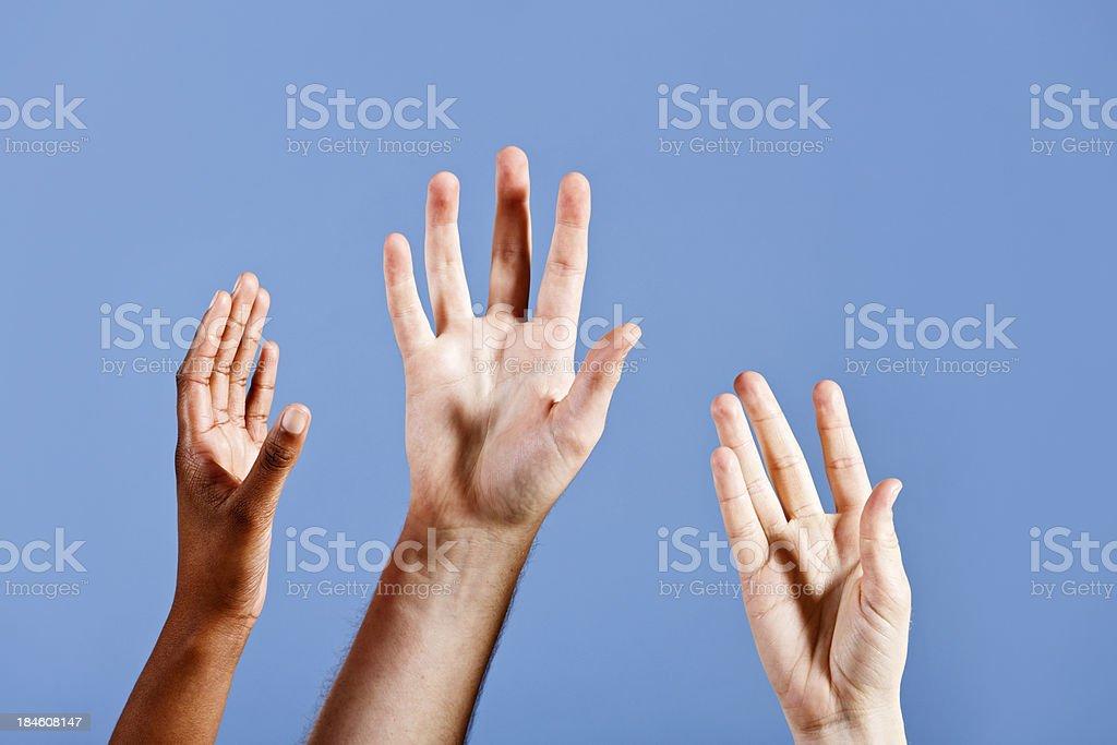 Three hands reach up longingly towards sky blue background royalty-free stock photo