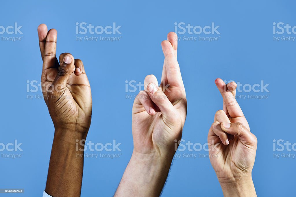 Three hands with fingers crossed for luck, against blue background stock photo