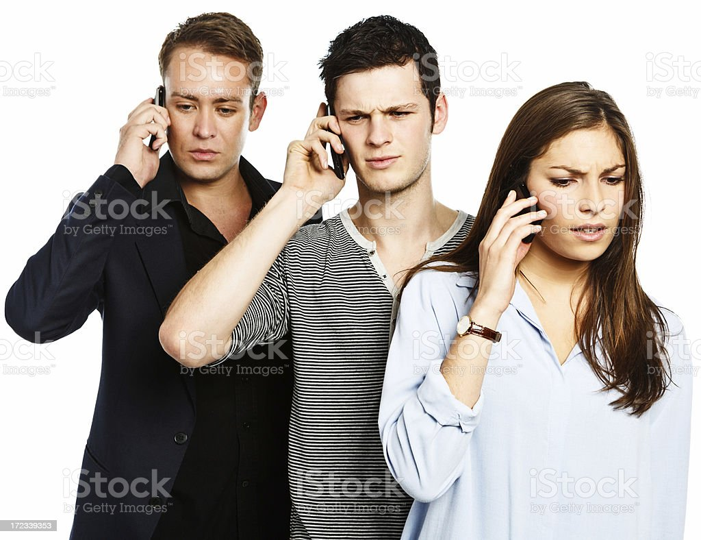 Three handsome youngsters hear bad news on cell phones royalty-free stock photo