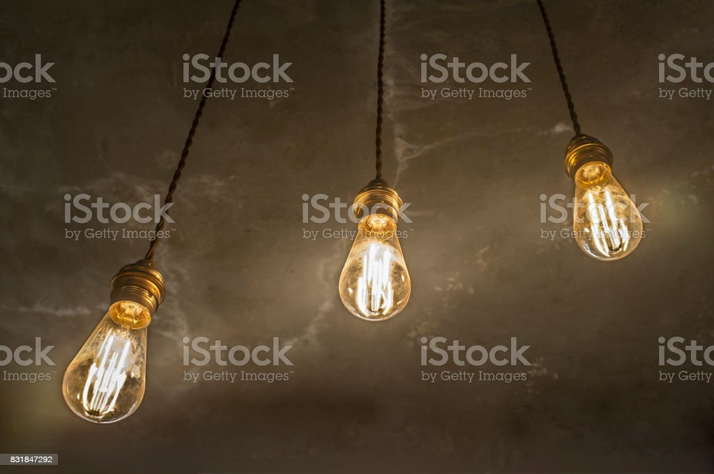 Three hanging light bulbs over oxide dark color concrete background stock photo