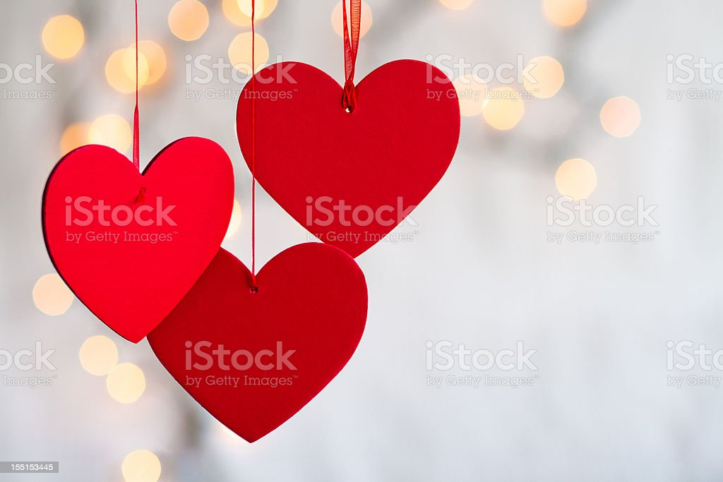 Three hanging red hearts on defocused light background. royalty-free stock photo