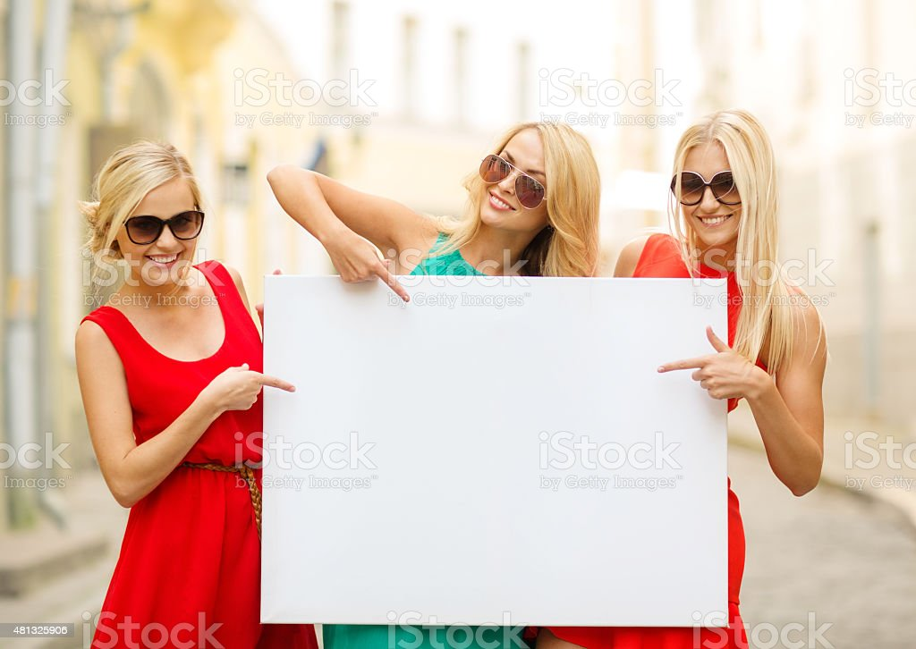 three happy blonde women with blank white board stock photo