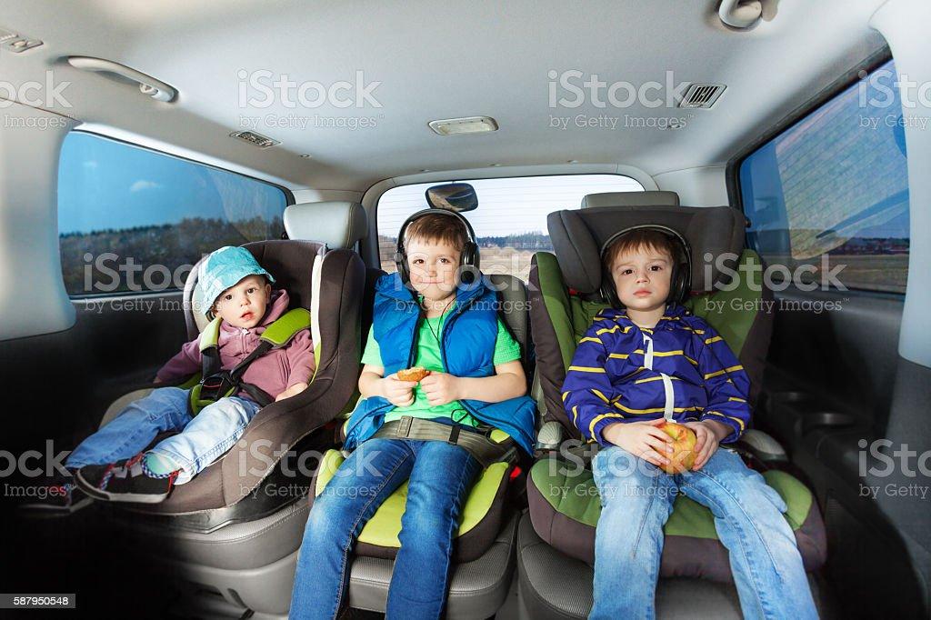 Three happy boys sitting in safety car seats stock photo