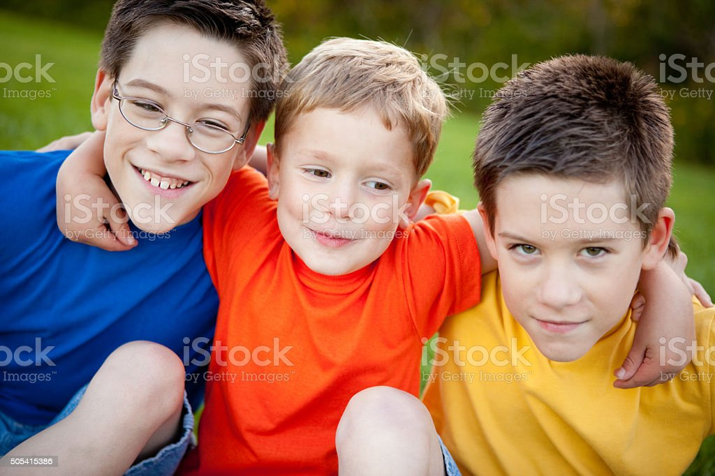 Three Happy Boys Sitting Together Outside stock photo