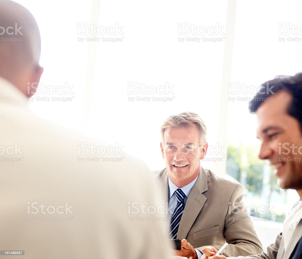 Three happy business colleagues in meeting royalty-free stock photo