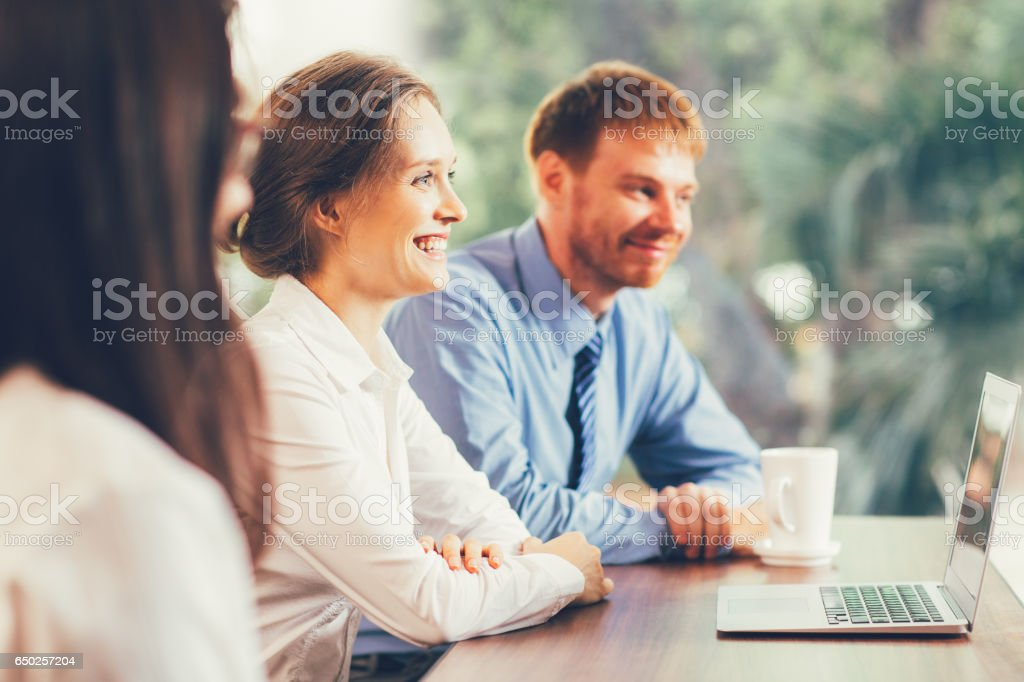 Three Happy Business People Listening to Colleague stock photo
